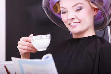 Girl reading magazine drinking coffee. Hairdryer in hair salon