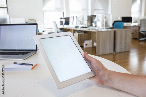 Person in the office holding a touch screen device.