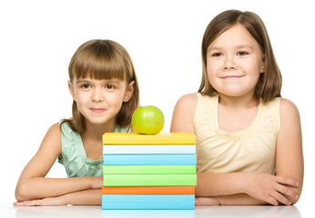 Little girls with books and apple