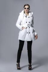 full length shot of beauty girl in white coat posing gray