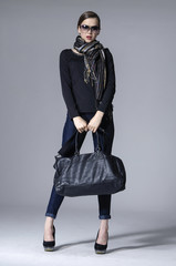 young elegant woman in sunglasses with scarf holding bag posing