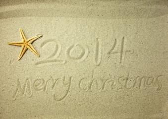 Merry Christmas 2014 handwritten in sand on a beautiful beach