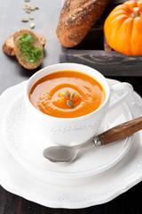 Pumpkin soup with pumpkin seeds, bread, and raw pumpkin