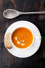 Pumpkin soup with pumpkin seeds on a wooden background