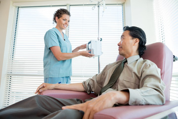 Nurse Looking At Patient While Adjusting IV Machine