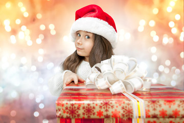 Child in Santa hat with gift box.