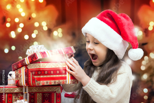 Happy Girl in Santa Hat Opening a Gift Box