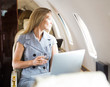 Businesswoman Looking Through Window Of Private Jet - 59313160