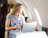 Businesswoman Looking Through Window Of Private Jet