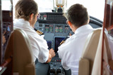 Pilots Operating Controls Of Corporate Jet