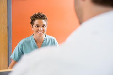 Nurse Looking At Patient In Hospital