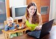 Happy young mother working with laptop and baby