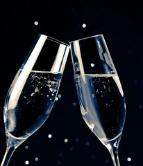 two champagne flutes on black dark light bokeh background