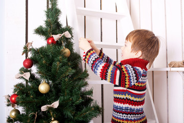 Christmas Eve concept, child decorating Christmas tree