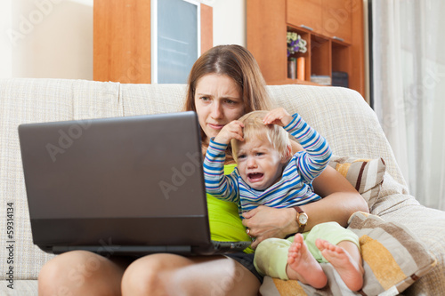 sorehead mother with crying baby working online