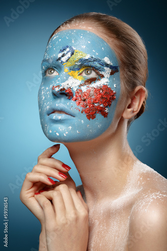 Beautiful fashion model with face art in winter style. Textural