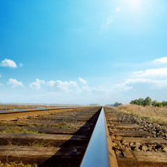 hot sun in blue sky over old railroad
