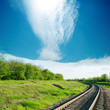 sky with cloud over railroad in green landscape