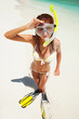 Fun woman with snorkeling equipment on the beach
