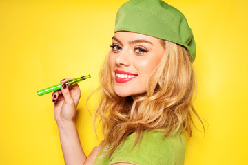 Trendy woman in green with an e-cigarette