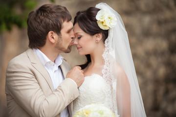 Bride and groom at wedding day kissing at park