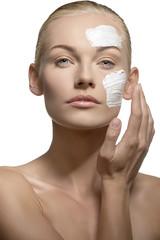 woman applying cream on face