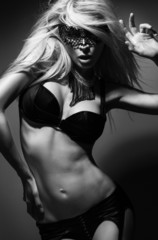 Beautiful, sexy blond woman in black underwear and mask black an