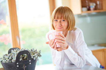 Happy mid aged woman with coffee at home