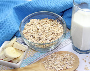 Oat flakes in bowl, milk and bananas