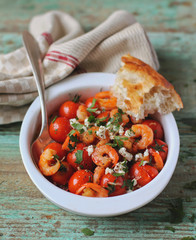Portion of baked cherry tomatoes and roasted shrimps