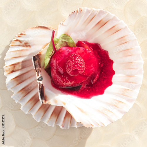 Scallop with raspberries on a plate, closeup