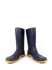 Pair of dark blue dirty rubber boots over a white background
