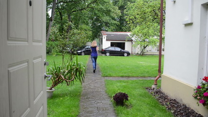 Lady in blue run through path from house to car in rainfall