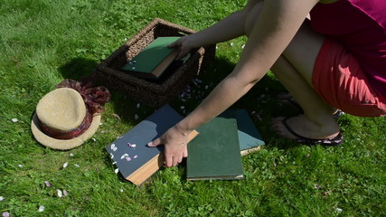 Student woman come and pick old books to wicker basket on lawn.