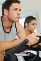 Young man and woman working out at spinning class