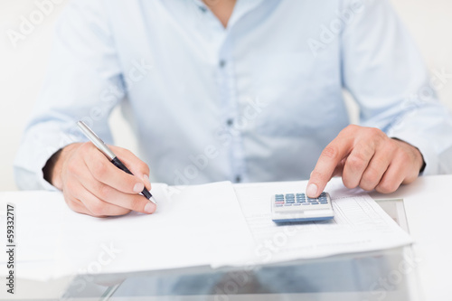 Mid section of a young man with bills and calculator