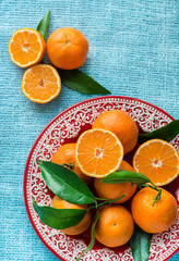 Tangerines on plate over light blue background