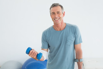 Mature man with crutch and dumbbells at gym hospital