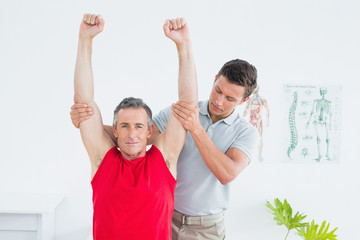 Physiotherapist stretching a mature mans arms