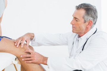 Side view of a mature doctor examining patients knee