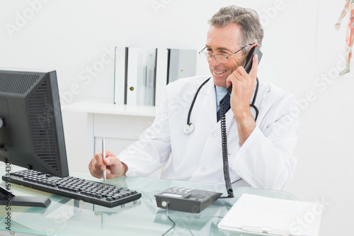 Doctor using computer and telephone at office
