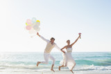 Newlyweds having fun holding balloons