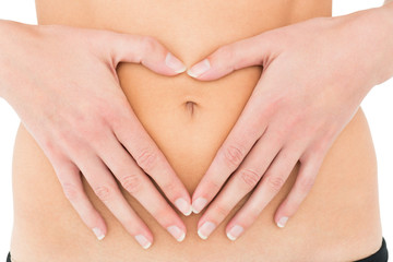Mid section of a fit woman with hands over belly
