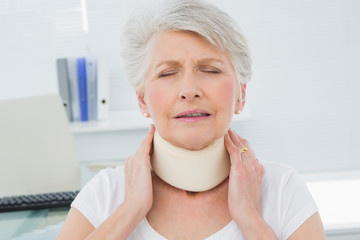 Senior woman wearing cervical collar in medical office