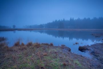 wild lake in dense autumn fog