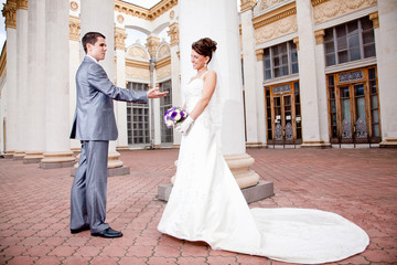 groom giving hand to beautiful bride in dress with long loop