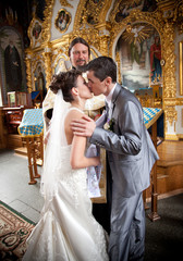 Just married couple kissing in orthodox church first time
