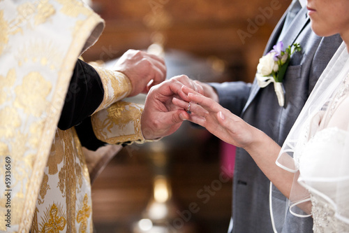orthodox bishop putting golden rings on bride and grooms hands