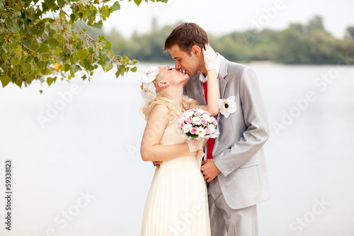 Beautiful just married couple kissing passionately on riverbank