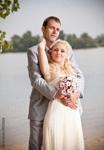 portrait of young bride and groom embracing on riverbank